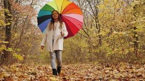 Passeggiata attraverso il parco di autunno Ragazza che cammina con l'ombrello stock footage