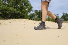 Passeggiata attraverso la sabbia con l'escursione delle scarpe Fotografia Stock