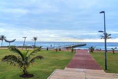 Passeggiata che conduce verso Pier Beach e l'orizzonte nuvoloso blu Fotografia Stock