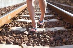 Passeggiata da solo sui binari ferroviari alla stazione ferroviaria fotografia stock