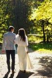 Passeggiata del fidanzato con la sposa sul suo braccio nel parco Immagine Stock