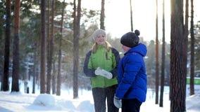 Passeggiata del figlio e della madre nella foresta di inverno video d archivio