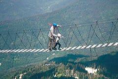 Passeggiata del ragazzo e dell'uomo lungo il ponte di corda immagini stock libere da diritti