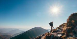 Passeggiata del viaggiatore di viaggiatore con zaino e sacco a pelo del ragazzo su sul sole della cima della montagna al contrari fotografie stock