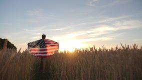 Passeggiata dell'uomo con la bandiera dell'America nel campo video d archivio