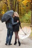 Passeggiata della donna e dell'uomo sotto gli ombrelli Fotografia Stock Libera da Diritti