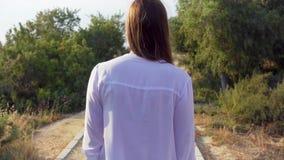 Passeggiata della donna lungo il passaggio pedonale in parco verde al rallentatore Natura godente femminile felice all'aperto da  stock footage
