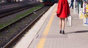Passeggiata della donna nel binario della stazione che tiene bagagli Immagini Stock Libere da Diritti
