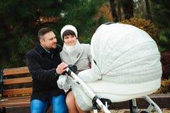 Passeggiata della famiglia nel parco di autunno con una carrozzina Aria aperta della mamma, del papà e del bambino fotografia stock libera da diritti