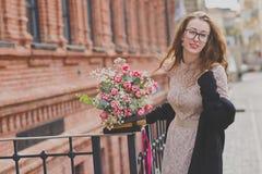 Passeggiata della primavera di una ragazza con un mazzo del fiore fotografia stock