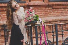Passeggiata della primavera di una ragazza con un mazzo del fiore immagine stock