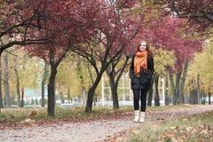 Passeggiata della ragazza della testarossa sulla via nel parco della città, stagione di caduta Fotografie Stock Libere da Diritti