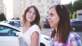 Passeggiata delle amiche intorno alla città Le ragazze camminano intorno alla città, parlando, divertendosi stock footage
