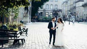 Passeggiata delle coppie sorridenti felici della persona appena sposata attivamente che parlano e che si tengono per mano Posizio Fotografia Stock
