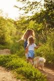 Passeggiata delle sorelline con il cane immagini stock