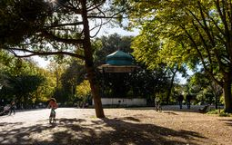 Passeggiata e bambini della gente che guidano le bici in Jardim da Estrela, Lisbona - Portogallo immagini stock libere da diritti