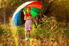 Passeggiata felice della ragazza del bambino con l'ombrello multicolore sotto pioggia immagine stock libera da diritti