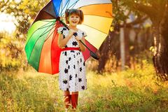 Passeggiata felice della ragazza del bambino con l'ombrello multicolore sotto pioggia fotografie stock libere da diritti