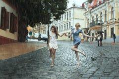 Passeggiata femminile degli amici nella pioggia Fotografie Stock