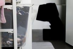 Passeggiata in gabinetto che conduce al bagno, mostrando canestro dei vestiti ed asciugamano nero che appende sopra la vasca Desc fotografia stock
