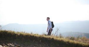 Passeggiata sola nelle montagne Il giovane bello cammina lungo la collina con uno zaino sulle sue spalle e guarda intorno archivi video