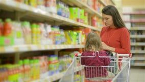 Passeggiate del bambino e della madre lungo gli scaffali all'ingrosso e merci di presa in carrello del negozio, bello giovane acq video d archivio