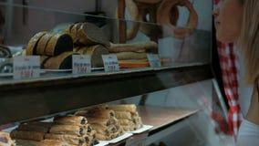 Passeggiate della donna nel caffè dei dolci del forno per comprare spuntino all'interno stock footage