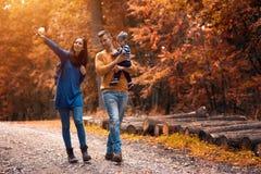 Passeggiate nel bosco di una coppia dei giovani con un ragazzino Fotografia Stock