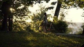 Passeggiate teenager con la bici in parco stock footage