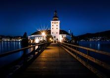 Passeio à beira mar iluminado ao Schloss Ort em Gmunden na hora crepuscular imagens de stock royalty free