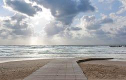 Passeio à beira mar na praia em um dia nebuloso fotos de stock