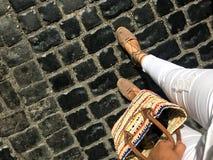 Passeio abaixo da rua A imagem mostra os pés da mulher e uma rua de pedra Imagem de Stock