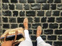 Passeio abaixo da rua A imagem mostra os pés da mulher e uma rua de pedra Fotos de Stock Royalty Free