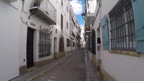 Passeio abaixo das ruas estreitas típicas da cidade espanhola pequena completamente das paredes brancas e do tempo morno do verão vídeos de arquivo