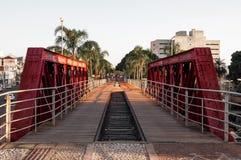Passeio a andar que atravessa uma ponte vermelha velha Fotografia de Stock Royalty Free
