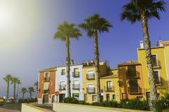 Passeio bonito com flores, palmeiras, árvores contra as casas coloridas da cidade antiga da Espanha de Villajoyosa fotografia de stock royalty free