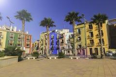 Passeio bonito com flores, palmeiras, árvores contra as casas coloridas da cidade antiga da Espanha de Villajoyosa imagens de stock royalty free