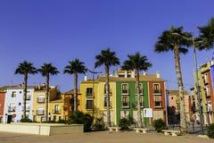 Passeio bonito com flores, palmeiras, árvores contra as casas coloridas da cidade antiga da Espanha de Villajoyosa foto de stock