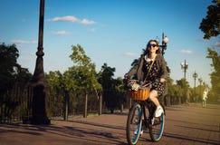 Passeio bonito da menina uma bicicleta do cruzador com as flores na cesta Fotografia de Stock Royalty Free