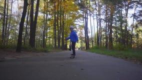 Passeio da criança do menino do skater no patim exterior no parque do outono