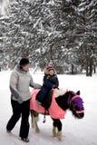 Passeio da criança um pônei no parque do inverno com mamã Fotos de Stock Royalty Free
