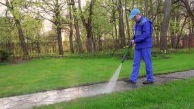 Passeio da lavagem do homem do jardineiro com o jato de água de alta pressão video estoque