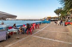 Passeio da margem com os povos que apreciam as barras exteriores na tarde na vila de Sferracavallo, província de Palermo, Sicília fotos de stock royalty free