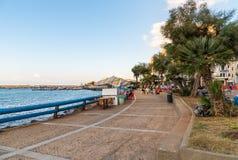 Passeio da margem com os povos que apreciam as barras exteriores na tarde na vila de Sferracavallo, província de Palermo, Sicília imagem de stock