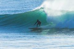 Passeio da onda do surfista mostrado em silhueta Fotografia de Stock