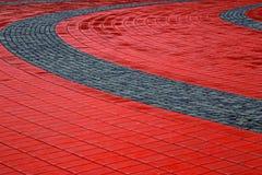 Passeio da pedra feito de pedras vermelhas e cinzentas cúbicas Imagem de Stock