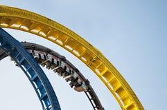 Passeio dando laços do roller coaster na feira de divertimento Fotografia de Stock