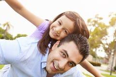 Passeio de Giving Daughter Piggyback do pai no jardim Imagens de Stock