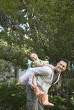 Passeio de Giving Daughter Piggyback do pai no parque Fotografia de Stock