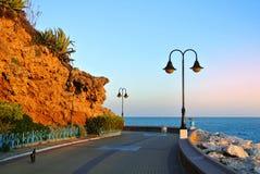 Passeio de Torremolinos, de uma estrada, de umas rochas, de arbustos de florescência e de mar Mediterrâneo Foto de Stock Royalty Free
